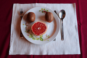 The plate with kiwi, cutlery and tablecloth