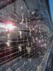 Melting snow on weldmesh of an outdoor aviary with sun flare light effects from the low winter sun. Vertical.