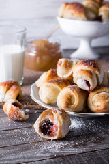 Rugelach with jam filling on plate with milk on wooden background - a traditional European pastry