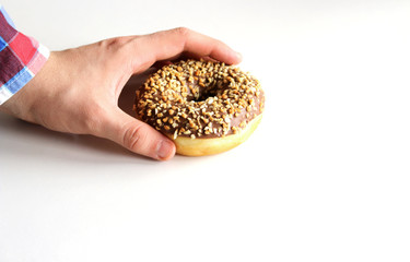 Donut in man's hand isolated on white background.Top view.