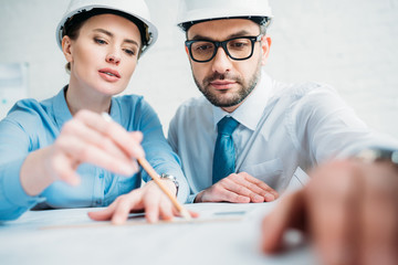 close-up shot of architects working with building plan at office