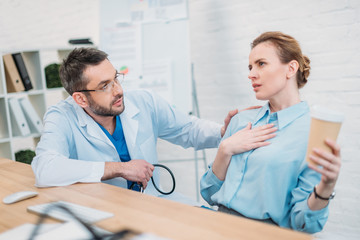 doctor giving consultation for female patient at workplace in office