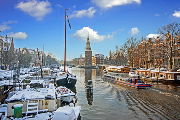 Snowy Amsterdam with the Montelbaan tower in winter in the Netherlands