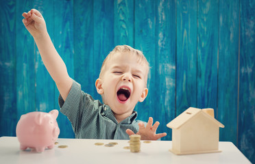 two years old child sitting on the floor and putting a coin into a piggybank Wall mural