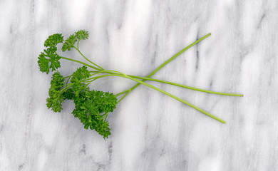 Top view of several curly parsley sprigs on a gray marble cutting board.