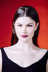 Portrait of beautiful young woman model with beautiful makeup in the Studio in a black shirt on a red background