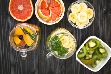 Glass jars and a glass of detox water with fresh fruit and herbs and ingredients on the table: grapefruit, chopped kiwi and slices banana in bowls, black wooden background, top view