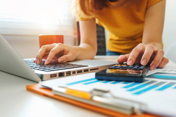 businesswoman hand working with finances about cost and calculator and laptop with tablet on withe desk at office in morning light