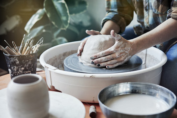 Ceramic studio, craft working process with clay potter's wheel, close-up of hands doing a pot or a vase, object