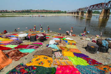 People dye traditional clothes on riverbank