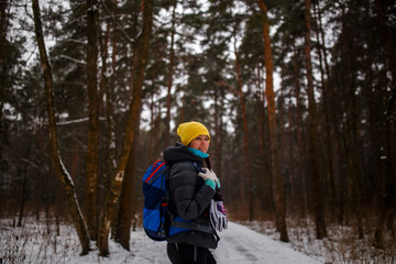 Side view of girl with backpack in winter forest