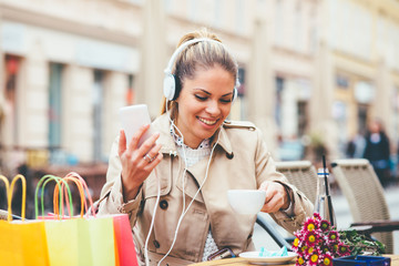 Young woman after shopping drinks coffee and listen music via headphones