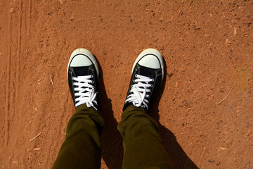 2 legs of adult man wear green trouser with black and white shoe stepped on soil ground