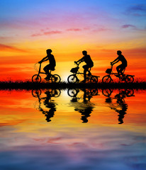 Silhouette group  bike relaxing and water reflection  on blurry sunrise background