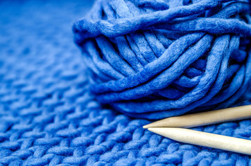 A bundle of blue merino yarn and bamboo knitting needles on a tied blue plaid.