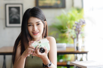 Happy Asian woman holding vintage camera in cafe, lifestyle concept.
