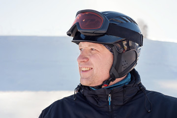 side portrait of a man in a ski helmet and ski goggles on the background of a ski snowboard descent from the mountain