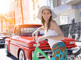 Beautiful girl with hat riding bike in Miami beach