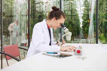 young female researcher examining a sample from the greenhouse