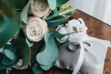Wedding bouquet of white roses and rings on white pillow