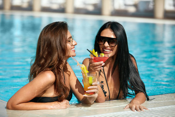 Girls In Pool At Summer. Beautiful Women With Drinks In Pool