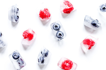ice cubes with fresh berries on white background top view