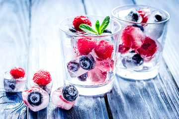 Frozen berries in glass for cocktail on wooden table background