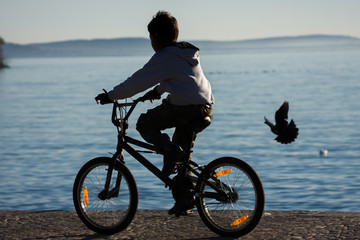 Silhouette of a child who rides a bicycle on the shore of the lake