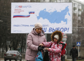 People walk near a board informing of the upcoming presidential election in Stavropol
