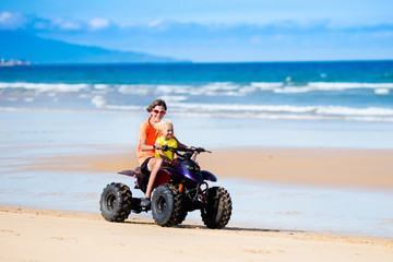 Kids on quad bike. Off road all terrain vehicle.