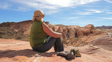 Active Woman Tourist Sitting Resting On Red Rock And Admiring Views Of Canyon