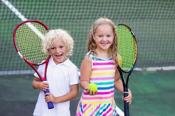 Children playing tennis on outdoor court