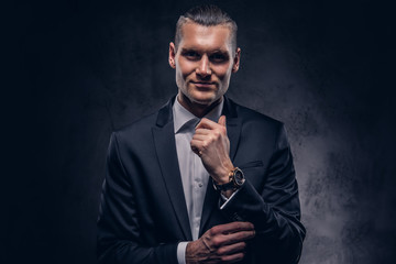 Handsome businessman against a dark background.
