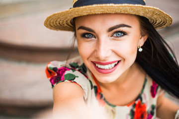 young beautiful girl in summer dress, straw hat. Selfie portrait. Travels around the European city in the summer. Cheerful, smiling lady. old houses, paving stones, vintage style, old Europe
