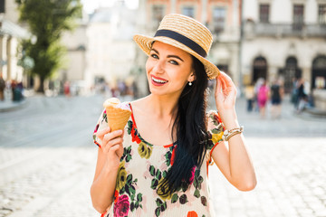 Young beautiful girl in summer dress, straw hat. Travels around the European city in the summer. A cheerful, smiling lady holds ice cream in her hands. Ancient houses, paving stones