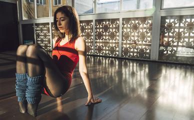 Young woman in bodysuit training in studio