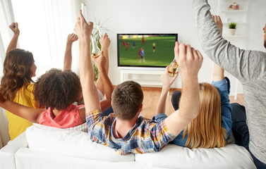 friends with beer watching soccer on tv at home