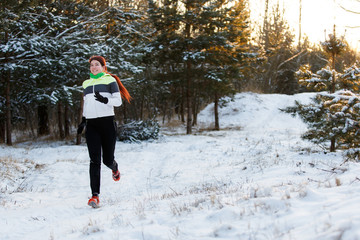 Photo of cheerful sportswoman in sneakers on morning run in winter forest