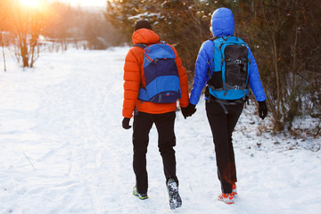 Picture from back of man and woman with backpacks in winter forest