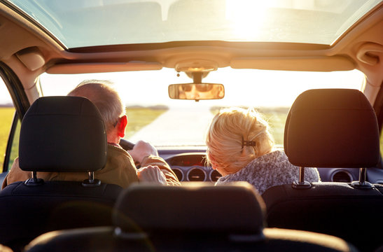 Smiling elderly couple driving car.