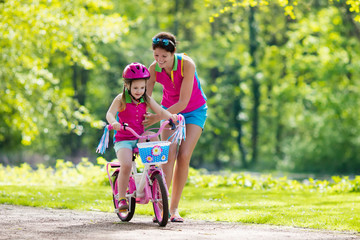 Mother teaching child to ride a bike