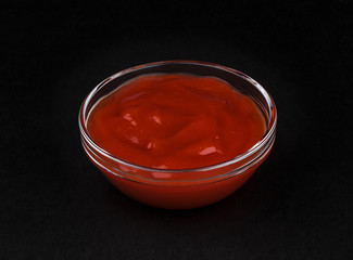 Ketchup in bowl on black background