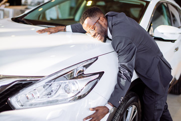 Visiting car dealership. Handsome black man is hugging his new car and smiling