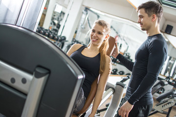 Fitness girl working out on exercise machine with support of handsome guy in gym.