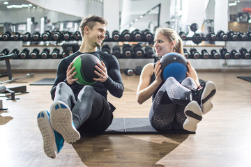 Fit couple doing abdominal exercise with fitness balls at gym.