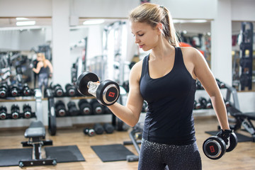 Portrait of fit blonde woman lifting weighs in the gym.