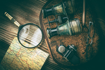 Magnifying glass and binoculars on the old map.