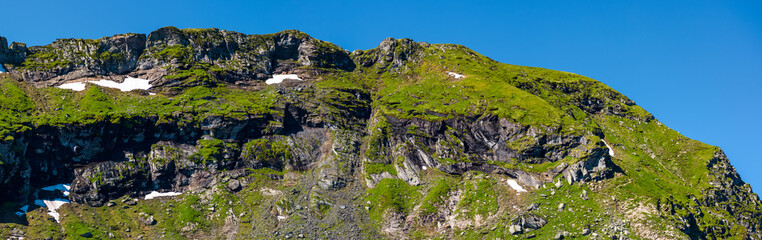 mountain ridge with rocky cliffs and grassy slopes. beautiful nature scenery of Fagaras mountains, Romania