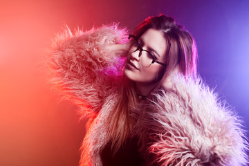 Fashionable young woman in a fluffy pink coat, neon light. Portrait of a beautiful trendy girl