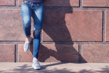 Girl in jeans and sneakers on the street